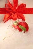 Rote Weihnachtskugel im Schnee Lizenzfreies Stockfoto