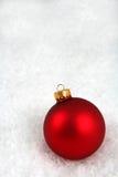 Rote Weihnachtskugel im Schnee Stockbilder