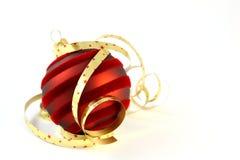 Rote Weihnachtskugel mit lockigen Farbbändern auf Weiß Lizenzfreie Stockfotos