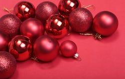 Rote Weihnachtskugeln auf einem roten Hintergrund Stockfotos