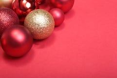 Rote Weihnachtskugeln auf einem roten Hintergrund Lizenzfreie Stockbilder
