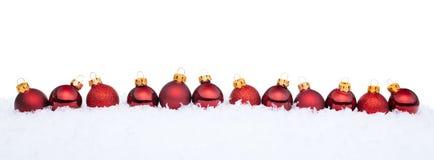 Rote Weihnachtskugeln auf Schnee Lizenzfreies Stockbild
