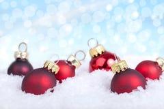 Rote Weihnachtskugeln auf Schnee Stockfotos