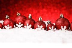 Rote Weihnachtskugeln auf Schnee Lizenzfreie Stockfotografie