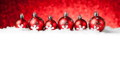 Rote Weihnachtskugeln auf Schnee Stockbild