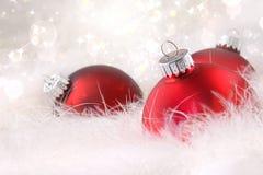 Rote Weihnachtskugeln in den weißen Federn Stockbild