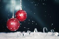 Rote Weihnachtskugeln, -farbband und -schnee stockfotografie
