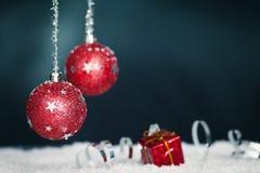 Rote Weihnachtskugeln, -farbband und -schnee lizenzfreie stockfotografie