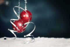 Rote Weihnachtskugeln, -farbband und -schnee Stockfotos