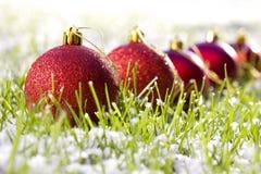 Rote Weihnachtskugeln im Schnee Stockfotografie