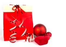 Rote Weihnachtskugeln und anwesender Beutel des Papiers auf Weiß Stockfoto