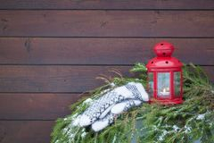Rote Weihnachtslaterne mit einer Kerze und Wollskandinavischen Arthandschuhen Stockfotos
