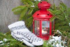 Rote Weihnachtslaterne mit einer Kerze und Wollskandinavischen Arthandschuhen Lizenzfreie Stockbilder