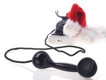 Rote Weihnachtsmann-Hüte und altes Telefon Stockfotos