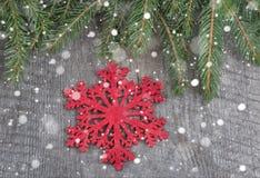 Rote Weihnachtsschneeflocken auf hölzernem Hintergrund Gezogener Schnee Stockfotos
