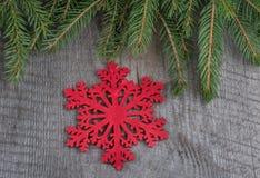 Rote Weihnachtsschneeflocken auf Hintergrund mit Tannenzweigen Gezogener Schnee Stockfoto