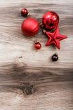 Rote Weihnachtsverzierungen auf einem rustikalen hölzernen Hintergrund Abbildung innen Glückliches neues Jahr Lizenzfreies Stockbild