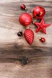 Rote Weihnachtsverzierungen auf einem rustikalen hölzernen Hintergrund Abbildung innen Glückliches neues Jahr Stockfotos