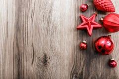 Rote Weihnachtsverzierungen auf einem rustikalen hölzernen Hintergrund Abbildung innen Glückliches neues Jahr Lizenzfreies Stockfoto