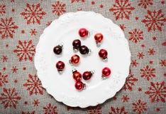 Rote Weihnachtsverzierungen auf Weiß Segeltuchhintergrund mit roten Funkelnschneeflocken Abbildung innen Glückliches neues Jahr Stockfotos