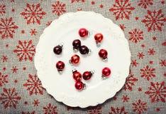 Rote Weihnachtsverzierungen auf Weiß Segeltuchhintergrund mit roten Funkelnschneeflocken Abbildung innen Glückliches neues Jahr p Lizenzfreie Stockfotografie