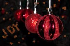 Rote Weihnachtsverzierungen, die in einer Reihe hängen Stockfotografie