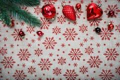 Rote Weihnachtsverzierungen (Kegel, Bälle) und Weihnachtsbaum auf Segeltuchhintergrund mit roten Funkelnschneeflocken Stockbild