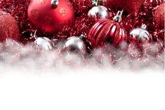 Rote Weihnachtsverzierungen und -girlande über weißer Leerstelle Stockbilder