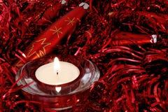 Rote Weihnachtsverzierungen und -kerze Stockfotografie