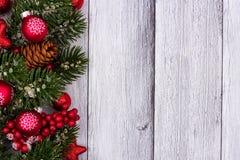 Rote Weihnachtsverzierungen und -niederlassungen versehen Grenze auf weißem Holz mit Seiten Stockfotografie