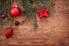 Rote Weihnachtsverzierungen und Tannenbaumast auf einem rustikalen hölzernen Hintergrund Abbildung innen Glückliches neues Jahr B Stockfotografie
