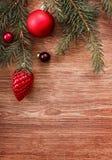 Rote Weihnachtsverzierungen und Tannenbaumast auf einem rustikalen hölzernen Hintergrund Abbildung innen Glückliches neues Jahr B Stockfoto