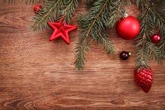 Rote Weihnachtsverzierungen und Tannenbaumast auf einem rustikalen hölzernen Hintergrund Abbildung innen Glückliches neues Jahr B Stockfotos