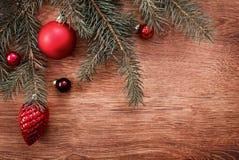 Rote Weihnachtsverzierungen und Tannenbaumast auf einem rustikalen hölzernen Hintergrund Abbildung innen Glückliches neues Jahr B Lizenzfreie Stockbilder
