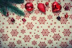 Rote Weihnachtsverzierungen und Weihnachtsbaum auf Segeltuchhintergrund mit roten Funkelnschneeflocken Abbildung innen Glückliche Stockbild