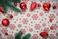 Rote Weihnachtsverzierungen und Weihnachtstanne auf Segeltuchhintergrund mit roten Funkelnschneeflocken Lizenzfreie Stockbilder