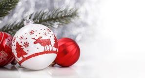 Rote Weihnachtsverzierungen und Weihnachtstanne auf Segeltuchhintergrund mit roten Funkelnschneeflocken Lizenzfreies Stockfoto