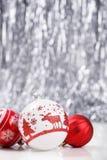 Rote Weihnachtsverzierungen und Weihnachtstanne auf Segeltuchhintergrund mit roten Funkelnschneeflocken Lizenzfreie Stockfotografie