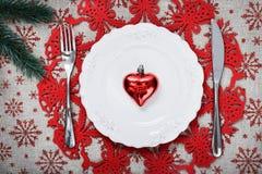 Rote Weihnachtsverzierungen und Weihnachtstanne auf Segeltuchhintergrund mit roten Funkelnschneeflocken Lizenzfreie Stockfotos