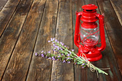 Rote Weinlesekerosinlampe und Lavendel blüht auf Holztisch. Konzept der schönen Kunst. Stockfoto