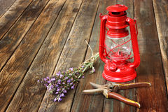 Rote Weinlesekerosinlampe und weise Blumen auf Holztisch. Konzept der schönen Kunst. Stockbilder