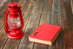 Rote Weinleselampe und rotes antikes Buch auf Holztisch. Weinlesestilllebendesign. Stockfotos