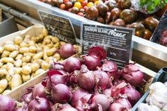Rote Zwiebeln und Kartoffeln in einem Markt mit französischem Preis unterzeichnen Lizenzfreie Stockfotos