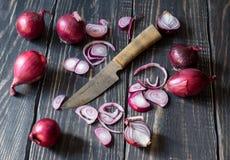 Rote Zwiebeln und Messer Stockfotografie