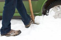 Rotelle di automobile di scavatura dell'uomo da neve Fotografie Stock