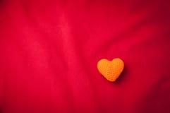 Roter abstrakter Hintergrund mit orange Herzform Lizenzfreies Stockbild
