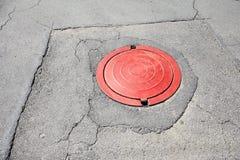 Roter Abwasserkanal auf Asphalt Lizenzfreies Stockfoto