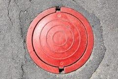 Roter Abwasserkanal auf Asphalt Stockfoto