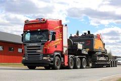 Roter Anhänger Scanias halb schleppt Hydraulikbagger Stockfoto