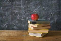 Roter Apfel auf Büchern mit Kreidebrett Stockbilder
